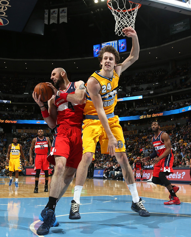 . Washington Wizards center Marcin Gortat, left, of Poland, wrestles away the rebound from Denver Nuggets forward Jan Vesely, of the Czech Republic, in the third quarter of an NBA basketball game in Denver on Sunday, March 23, 2014. The Nuggets won 105-102. (AP Photo/David Zalubowski)