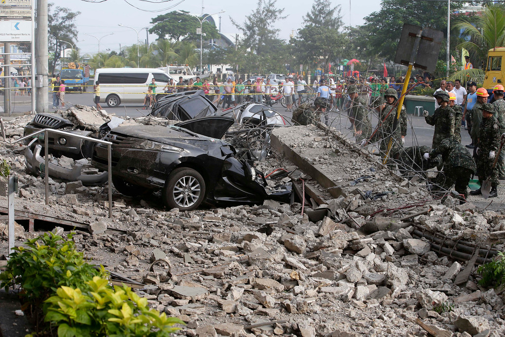 . Soldiers remove the debris that fell over cars following a 7.2-magnitude earthquake that hit Cebu city in central Philippines Tuesday, Oct. 15, 2013. The tremor collapsed buildings, cracked roads and toppled the bell tower of the Philippines\' oldest church Tuesday morning, causing multiple deaths across the central region and sending terrified residents into deadly stampedes. (AP Photo/Bullit Marquez)