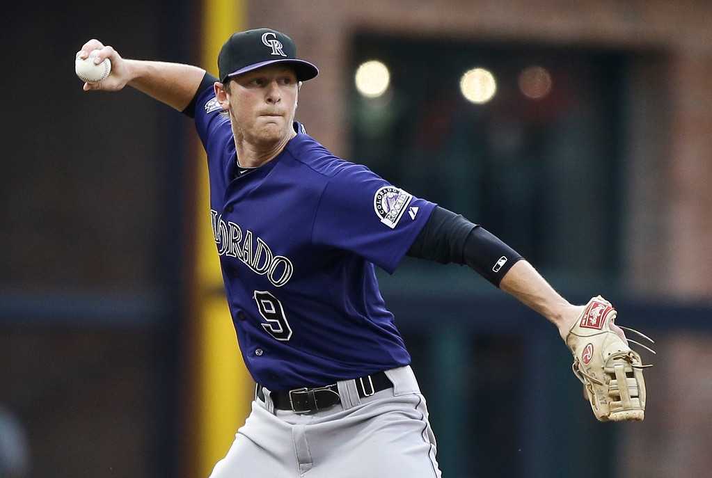 . Colorado Rockies third baseman DJ LeMahieu reaches back to make a throw to first to get San Diego Padres\' Carlos Quentin and save a run from scoring in the first inning of a baseball game in San Diego, Tuesday, July 9, 2013. (AP Photo/Lenny Ignelzi)