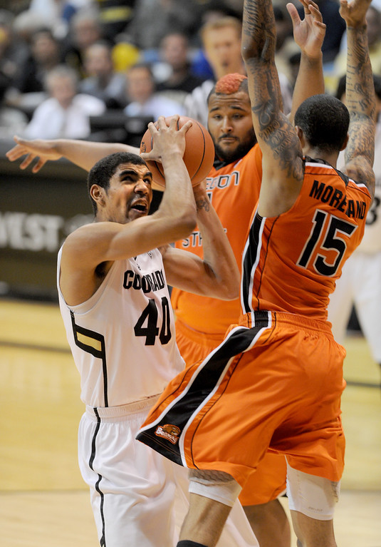 . Josh Scott of CU drives on Joe Burton, and Eric Moreland (15), both of OSU, during the second half of the March 9, 2013 game in Boulder.    (Cliff Grassmick/Boulder Daily Camera)