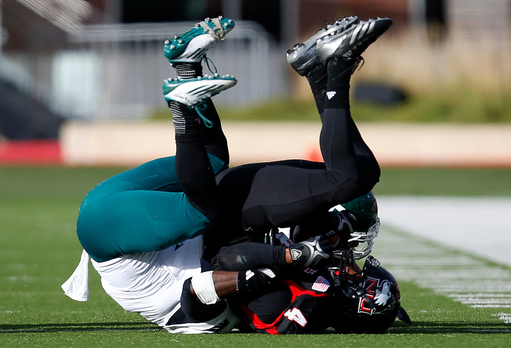 . Eastern Michigan defensive back Willie Creear, left, tackles Northern Illinois wide receiver Da\'Ron Brown, right, during the first half of an NCAA college football game on Saturday, Oct. 26, 2013, in DeKalb, Ill. Northern Illinois won the game 59-20. (AP Photo/Jeff Haynes)