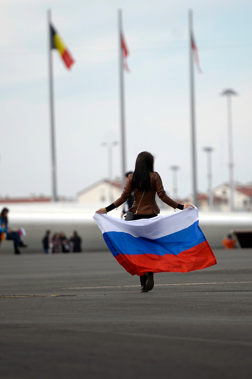 . Sochi, RUSSIA - FEBRUARY 13: Nadegda Pavlova walks with the Russian flag in the Sochi 2014 Olympic park. Sochi 2014 Winter Olympics on Friday, February 14, 2014. (Photo by AAron Ontiveroz/The Denver Post)
