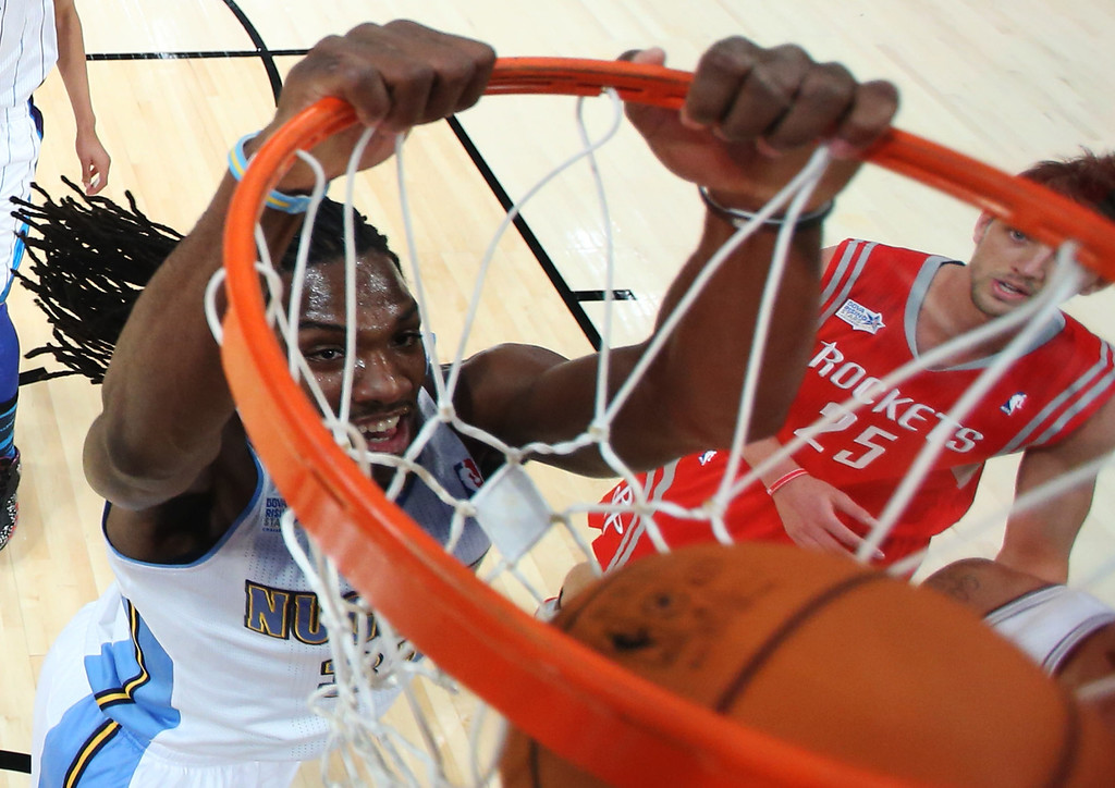 . Team Chuck\'s Kenneth Faried, of the Denver Nuggets, dunks as Team Shaq\'s Chandler Parsons, of the Houston Rockets, looks on during the first half of the Rising Stars Challenge basketball game at NBA All-Star Weekend, Friday, Feb. 15, 2013, in Houston. (AP Photo/Ronald Martinez, Pool)