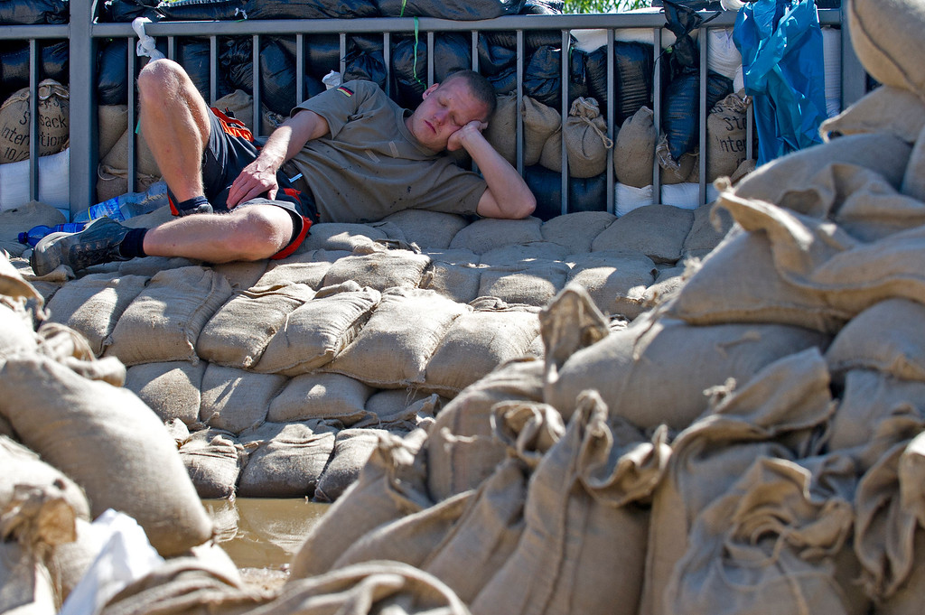 . A young men sleeps on stacked up sand bags after building a flood protection in a street flooded by the river Elbe in Dresden, eastern Germany, on June 5, 2013.   AFP PHOTO / ROBERT  MICHAEL/AFP/Getty Images