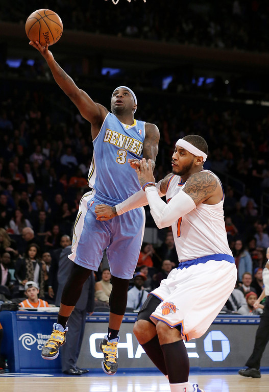 . Denver Nuggets\' Ty Lawson (3) drives past New York Knicks\' Carmelo Anthony (7) during the second half of an NBA basketball game Friday, Feb. 7, 2014, in New York. The Knicks won 117-90. (AP Photo/Frank Franklin II)