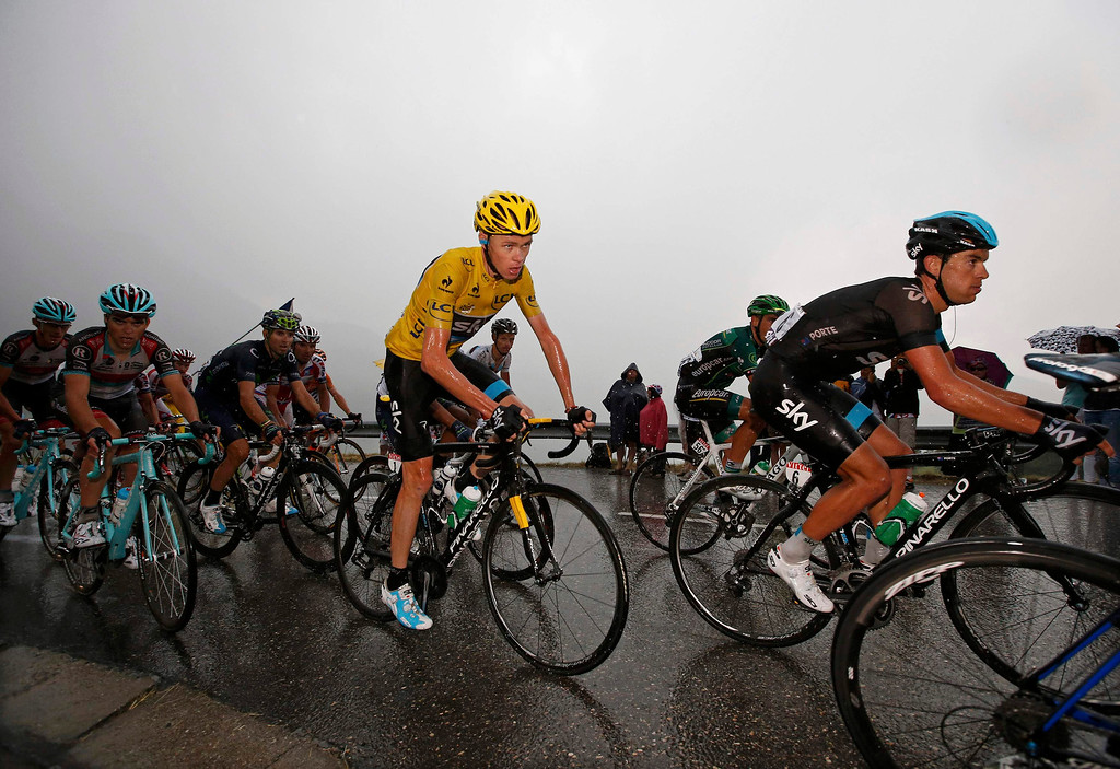 . Race leader jersey holder Team Sky rider Christopher Froome of Britain cycles in the pack under the rain during the 204.5 km stage of the centenary Tour de France cycling race from Bourg d\'Oisans to Le Grand Bornand, in the French Alps, July 19, 2013.  REUTERS/Eric Gaillard