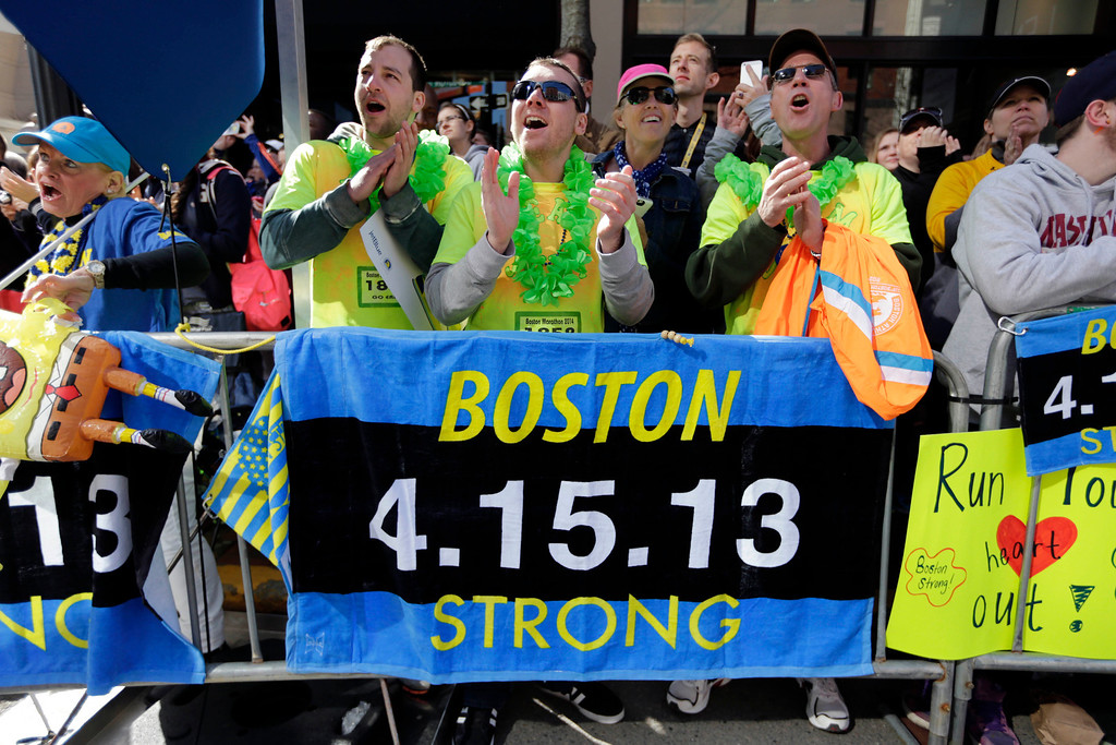 . Race fans from left, Andrew Lembecke, of Chicago, Brandon Petrich of Fargo, N.D, Marlene Youngblood of Louisville, Ky, and Bill Januszewski cheer near the finish line at the 118th Boston Marathon Monday, April 21, 2014 in Boston. (AP Photo/Robert F. Bukaty)