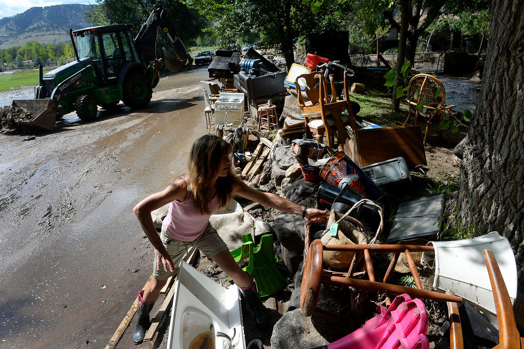 . BOULDER, CO. - SEPTEMBER 17: Cheryl Supino salvages items from a pile of belongings outside the home she share with her husband Kim Schuler on Upland Ave in Boulder, CO September 17, 2013. Thes property abuts Four Mile Creek and the home was flooded through out week. Colorado officials on Monday updated the number of people killed in the state�s floods to as many as eight, as rescue helicopters took to the skies and emergency operations continued. Flooding in 15 Colorado counties has destroyed 1,502 homes and damaged 17,494 leaving more than 11,000 people evacuated, according to the Colorado Office of Emergency Management. (Photo By Craig F. Walker / The Denver Post)