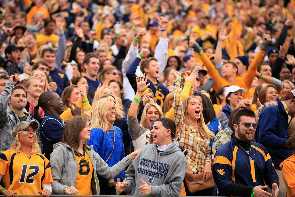 . West Virginia fans react to a touchdown during the second quarter of their NCAA college football game against Texas Tech in Morgantown, W.Va., on Saturday, Oct. 19, 2013. Texas Tech won 37-27. (AP Photo/Christopher Jackson)