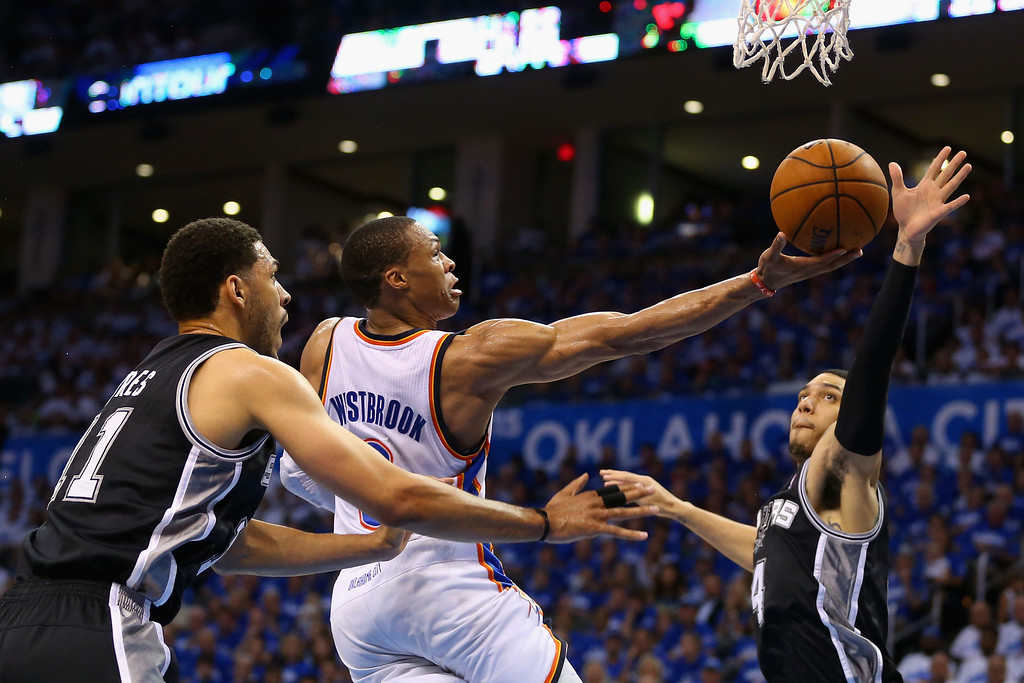 . OKLAHOMA CITY, OK - MAY 27: Russell Westbrook #0 of the Oklahoma City Thunder drives to the basket against Jeff Ayres #11 and Danny Green #4 of the San Antonio Spurs in the second half during Game Four of the Western Conference Finals of the 2014 NBA Playoffs at Chesapeake Energy Arena on May 27, 2014 in Oklahoma City, Oklahoma. (Photo by Ronald Martinez/Getty Images)