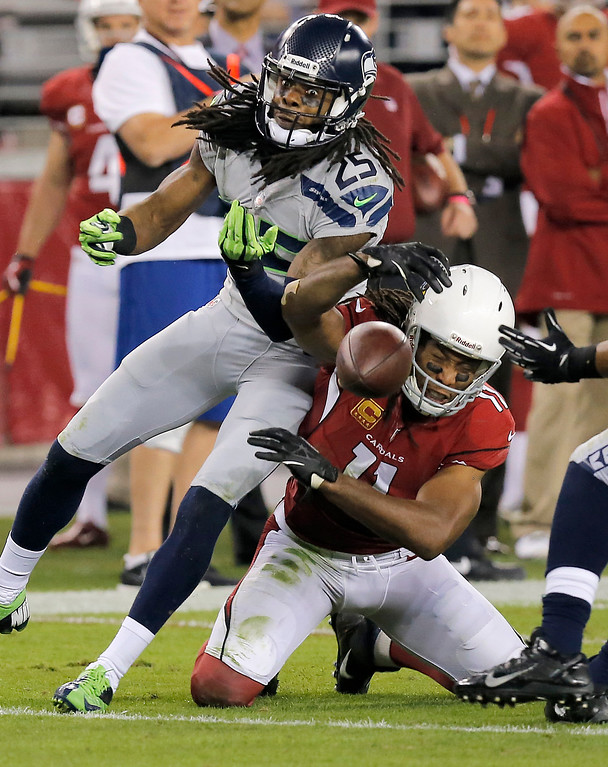 . Seattle Seahawks cornerback Richard Sherman (25) breaks up a pass intended for Arizona Cardinals wide receiver Larry Fitzgerald (11) during the second half of an NFL football game, Thursday, Oct. 17, 2013, in Glendale, Ariz. (AP Photo/Ross D. Franklin)