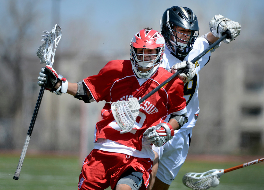 . LITTLETON, CO. - MAY 04:  Regis Jesuit\'s Bed Bechter passes Arapahoe\'s Chris Fons during the varsity high school lacrosse game between the Arapahoe Warriors and the Regis Jesuit Raiders in Littleton, CO May 04, 2013. The Raiders won the game 9-6.  (Photo By Craig F. Walker/The Denver Post)
