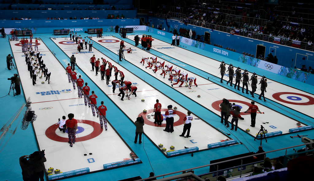 . This multiple expose shows men\'s curling teams competing during round robin matches at the 2014 Winter Olympics, Monday, Feb. 17, 2014, in Sochi, Russia. (AP Photo/Morry Gash)