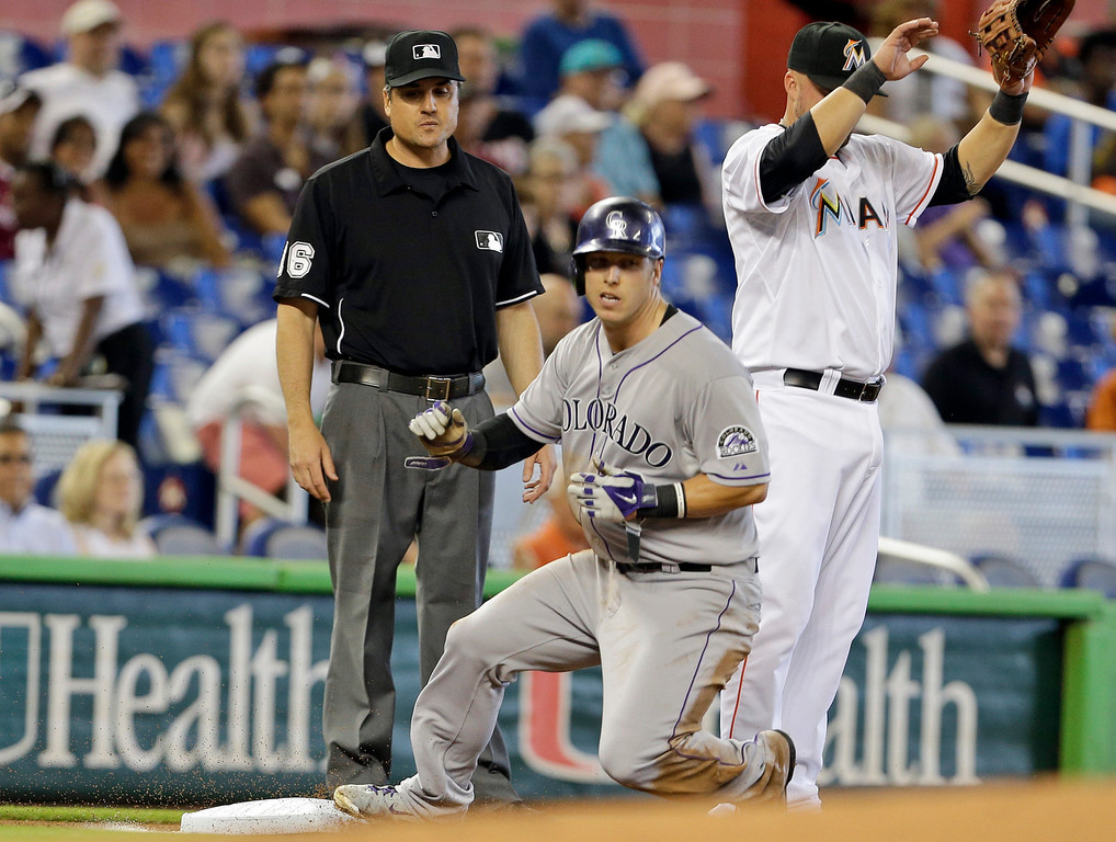 . Miami Marlins third baseman Casey McGehee, right, waits for the throw as Colorado Rockies\' Corey Dickerson, center, is safe at third on a throwing error by Miami Marlins\' catcher Jeff Mathis in the first inning of a baseball game, Thursday, April 3, 2014, in Miami. At left is third base umpire Mike DiMuro. (AP Photo/Lynne Sladky)