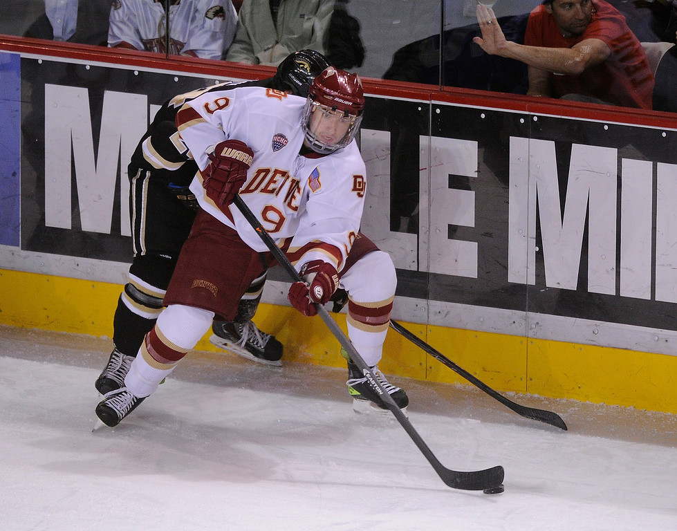 . DENVER, CO. - NOVEMBER 16: Denver center Gabe Levin (9) looked to make a pass off the boards in the first period. The University of Denver hockey team hosted Western Michigan at Magness Arena Saturday night, November 16, 2013.  Photo By Karl Gehring/The Denver Post