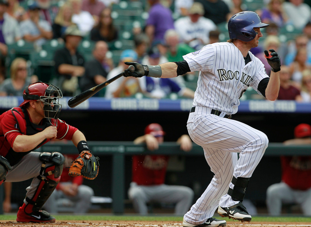 . Colorado Rockies\' Charlie Blackmon, right, singles as Arizona Diamondbacks catcher Miguel Montero looks on in the first inning of a baseball game in Denver on Sunday, Sept. 22, 2013. (AP Photo/David Zalubowski)