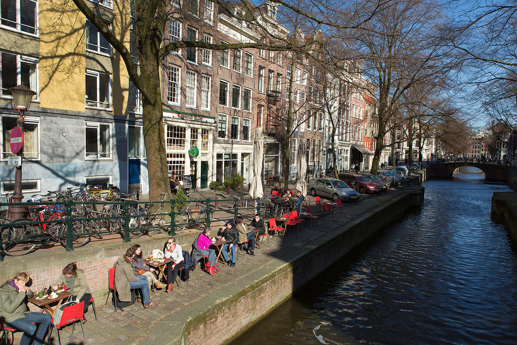 . People sit on a quay at the Leliegracht canal in Amsterdam April 2, 2013. The Royal celebrations in the Netherlands this week put the country and the capital Amsterdam on front pages and television screens around the world with an orange splash. There\'s plenty to see and do in 48 hours in this compact city, where the world-famous Rijksmuseum only recently reopened after an extensive renovation. Picture taken April 2, 2013. REUTERS/Michael Kooren
