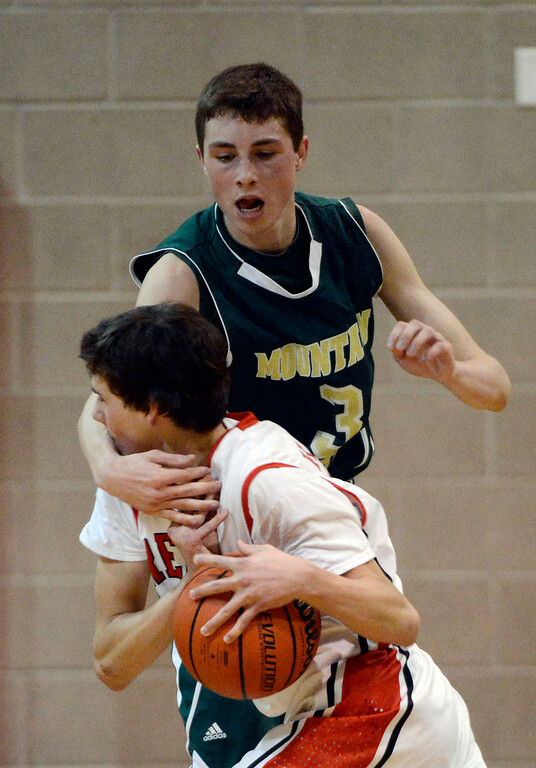 . LITTLETON, CO. - JANUARY 29: Regis Devin Kadillak (20) gets hit in the face by Mountain Vista Jake Pemberton (3) as he reaches in during their game January 29, 2013 at Regis.  (Photo By John Leyba / The Denver Post)