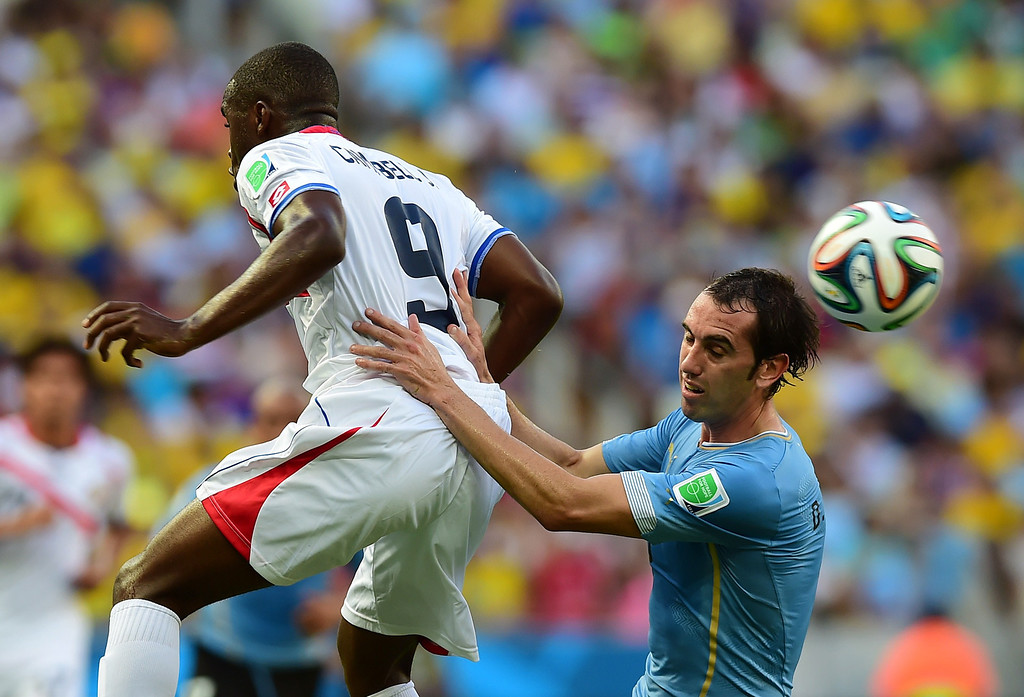 . Uruguay\'s defender Diego Godin (R) heads the ball next to Costa Rica\'s forward Joel Campbell during a Group D football match between Uruguay and Costa Rica at the Castelao Stadium in Fortaleza during the 2014 FIFA World Cup on June 14, 2014.  AFP PHOTO / RONALDO SCHEMIDT