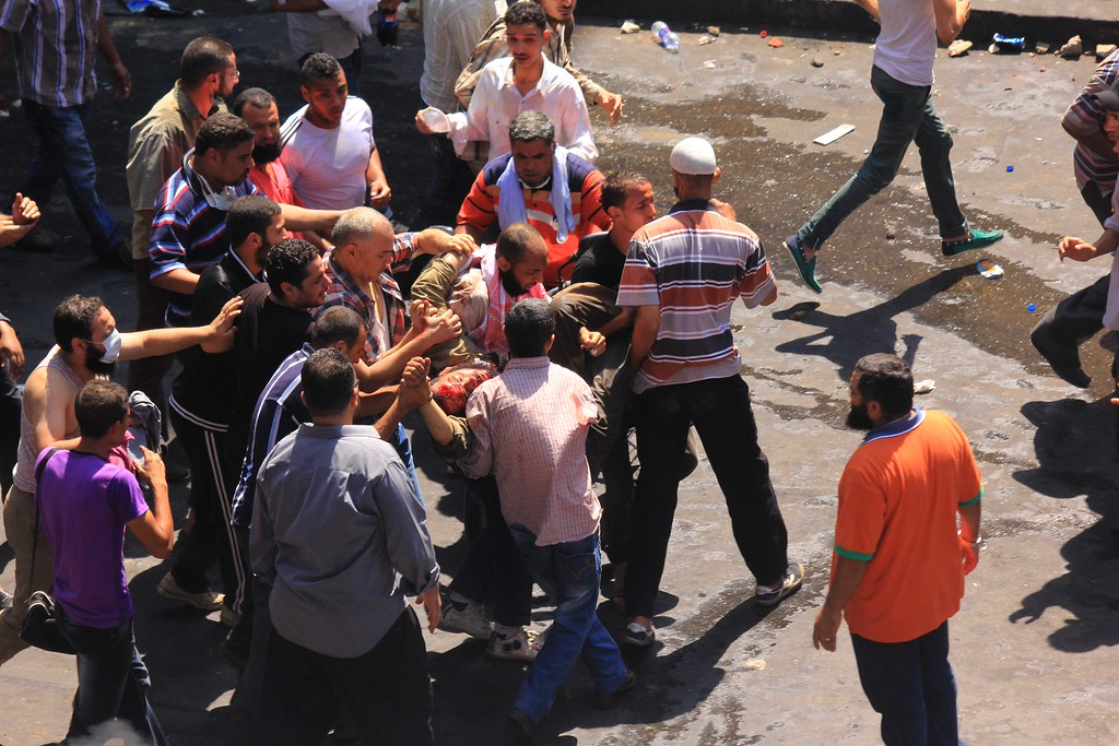 . Supporters of Egypt\'s ousted President Mohammed Morsi carry a wounded comrade during clashes with security forces near the largest sit-in by supporters of Morsi in the eastern Nasr City district of Cairo, Egypt, Wednesday, Aug. 14, 2013.  (AP Photo/Mohammed Abu Zeid)