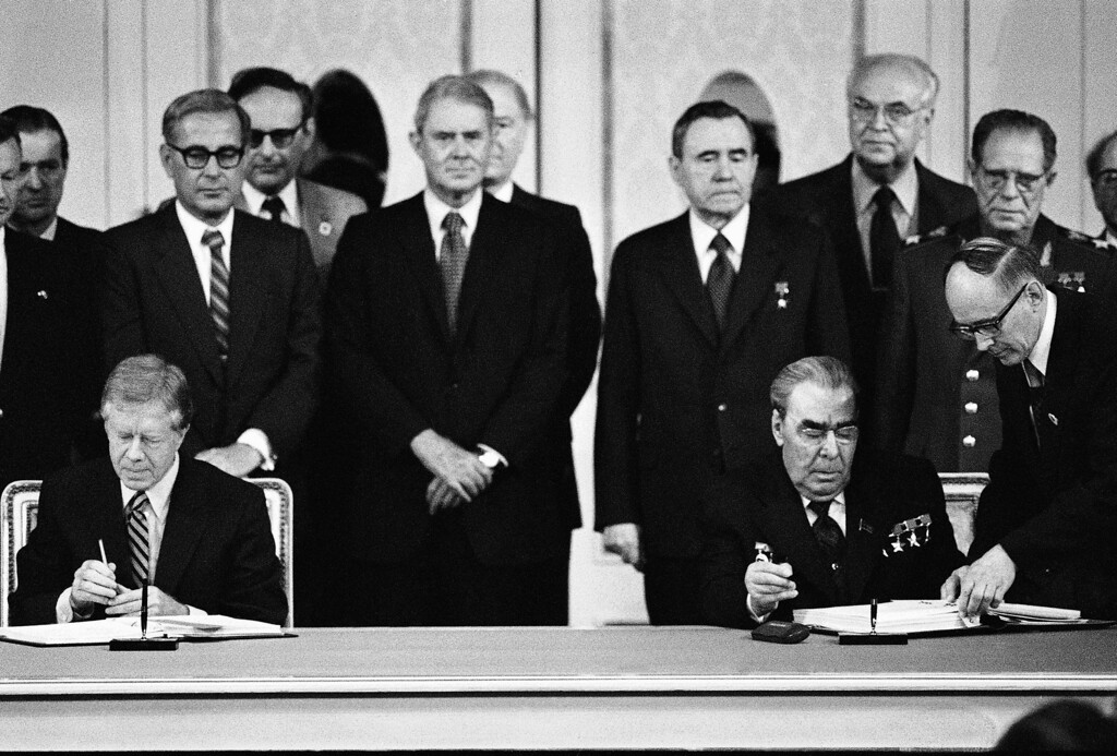 . Pres. Jimmy Carter, left, and Soviet President Leonid Brezhnev, right, sign the documents of the SALT II Treaty in the Vienna Imperial Hofburg Palace, Monday, June 18, 1979, Vienna, Austria. Behind the head of states are from left to right: National Security Advisor Zbigniew Brzezinski, Secretary of Defense Harold Brown, Secretary of State Cyrus Vance, Soviet Foreign Minister Andrej Gromyko, Anatoly Dobrynin, Soviet Ambassador to the U.S. and Dmitry Ustinov, Soviet Foreign Minister. (AP Photo)