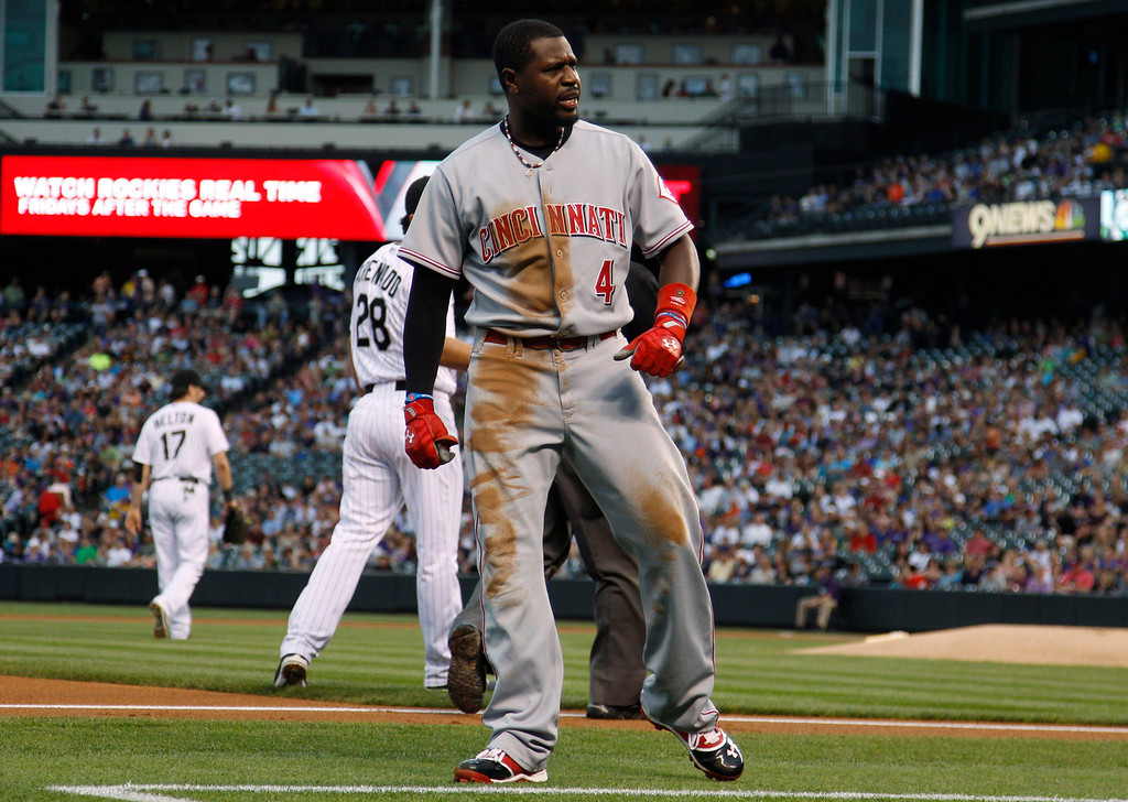 . Cincinnati Reds\' Brandon Phillips celebrates after his RBI-triple against the Colorado Rockies in the first inning of a baseball game in Denver on Saturday, Aug. 31, 2013. (AP Photo/David Zalubowski)