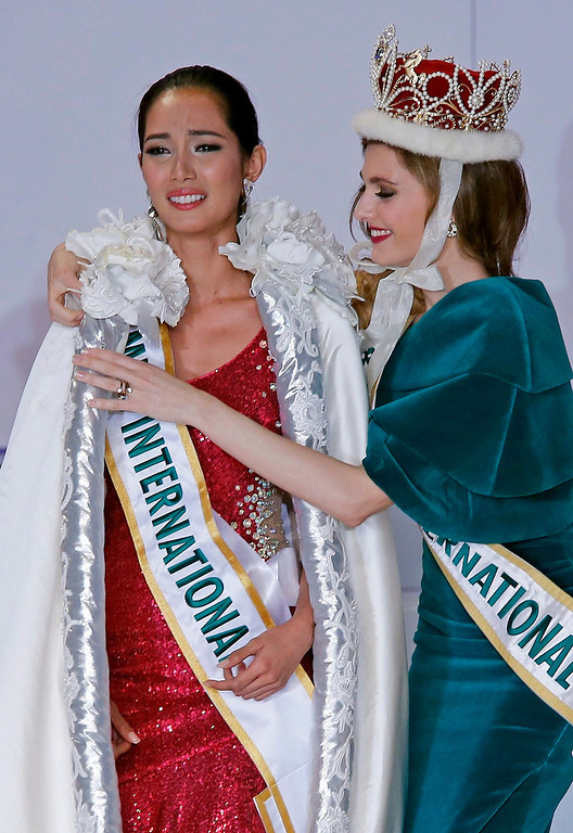 . Miss Philippines Bea Rose Santiago (L) receives a robe by 2008 Miss Spain and Miss International Alejandra Andreu (R) after winning the title of the 2013 Miss International beauty pageant in Tokyo, Japan, 17 December 2013.  EPA/KIMIMASA MAYAMA