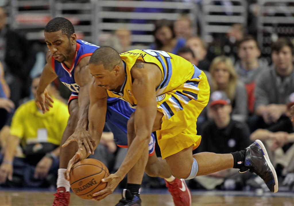 . Denver Nuggets\' Andre Miller (24)  and Philadelphia 76ers\' Hollis Thompson chase a loose ball  in the first  half of an NBA basketball game Saturday Dec. 7, 2013, in Philadelphia.  (AP Photo/H. Rumph Jr)