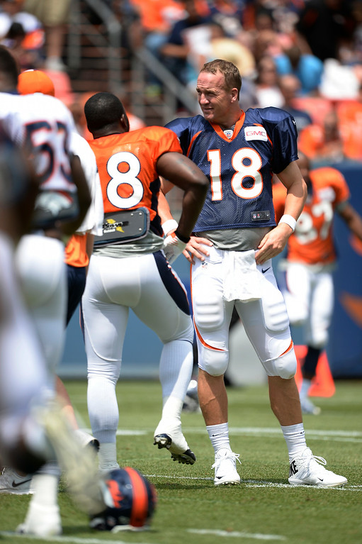 . Denver Broncos quarterback Peyton Manning (18) talks with Denver Broncos running back Montee Ball (28) on day four of the Denver Broncos 2014 training camp July 27, 2014 at Sports Authority Field at Mile High. (Photo by John Leyba/The Denver Post)