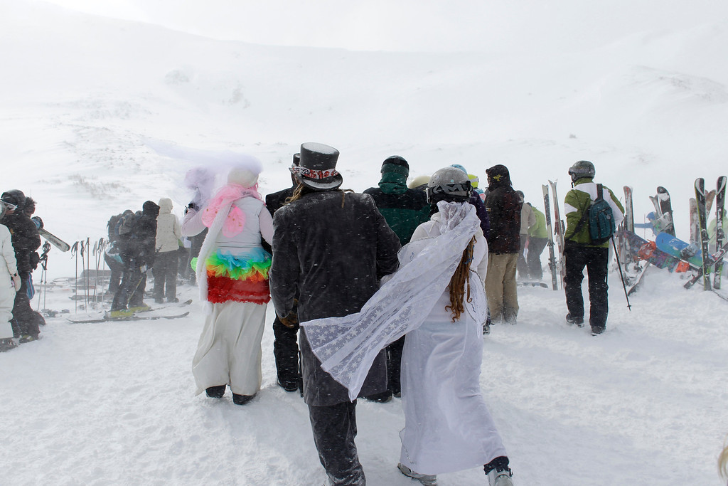 . A couple walk off together after joining eighty-seven other couples who gathered in a snow storm atop a mountain to get married or renew their vows, at the 22nd Annual Marry Me & Ski Free Mountaintop Matrimony, at Loveland Ski Area, in Colorado, Thursday, Feb. 14, 2013. (AP Photo/Brennan Linsley)
