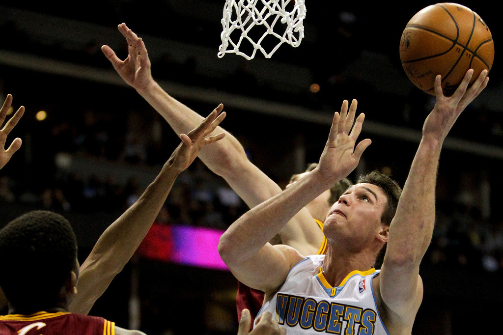 . Denver Nuggets\' Danilo Gallinari, right, lays one up over Cleveland Cavaliers\' C.J. Miles, left, during the second quarter of an NBA basketball game Friday, Jan. 11, 2013, in Denver. (AP Photo/Barry Gutierrez)