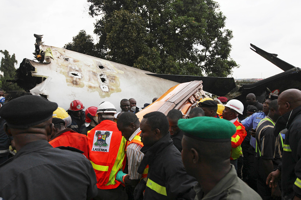 . Rescue workers remove a casket with the remains of former Ondo state governor Olusegun Agagu at the site of an Associated airline plane crash In Lagos, Nigeria , Thursday, Oct. 3, 2013,   (AP Photo/Sunday Alamba)