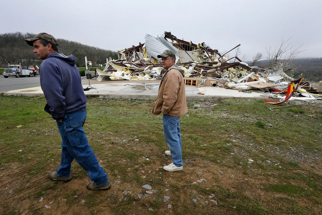 . Larry Gammill, left, who attends Botkinburg Foursquare Church, and his friend Tim Parks walk from what is left of the church in Botkinburg, Ark., Thursday, April 11, 2013 after a severe storm struck the building late Wednesday.  (AP Photo/Danny Johnston)