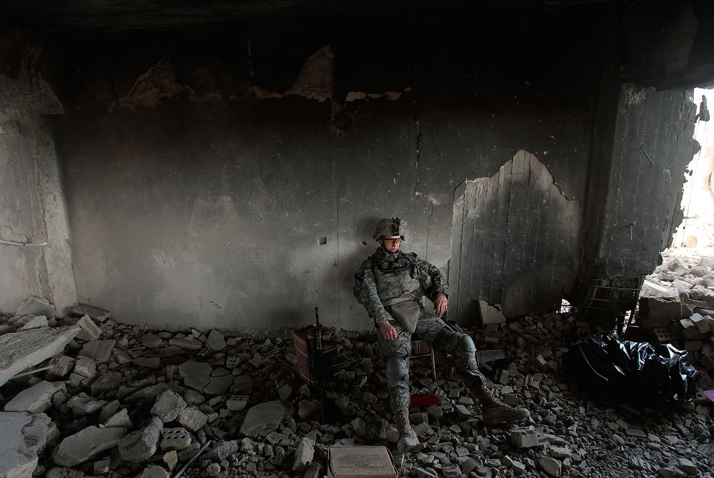 . Pft. Daniel Sims of Clemson, South Carolina of the 1st Battalion, 5th Cavalry Regiment of the U.S. Army sits during watch duties in a partially destroyed building that\'s being converted to an Army field post July 13, 2007 in the tense Amariyah neighborhood of Baghdad, Iraq.  Insurgents who were in control of Amariyah attempted to destroy this building and an adjacent bunker with explosives and burning tires, but the Army was able to salvage the compound.  (Photo by Chris Hondros/Getty Images)