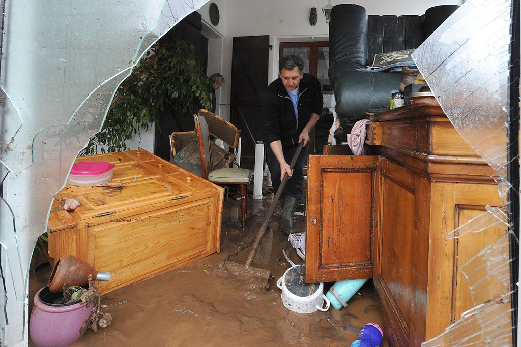 """. TOPSHOTS Peopleclean their house on Januray 20, 2014 in La Londe-les-Maures, southeastern France. River levels were receding early today in southeastern France after \""""historic\"""" floods left two people dead and more than 150 were airlifted to safety. A third man disappeared while out on his boat and 4,000 homes have been left without power after the deluge in the department of Var, they said. Local official Laurent Cayrel said one of the victims, a 73-year-old man, died in his basement, while the other was swept away in his car.  AFP PHOTO / BORIS HORVATBORIS HORVAT/AFP/Getty Images"""