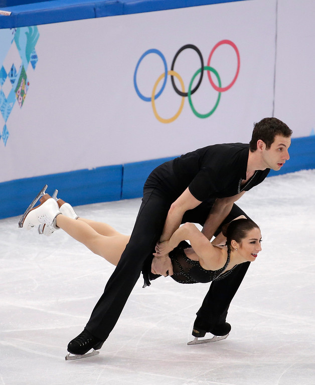 Description of . Marissa Castelli and Simon Shnapir of the United States compete in the pairs short program figure skating competition at the Iceberg Skating Palace during the 2014 Winter Olympics, Tuesday, Feb. 11, 2014, in Sochi, Russia. (AP Photo/Bernat Armangue)