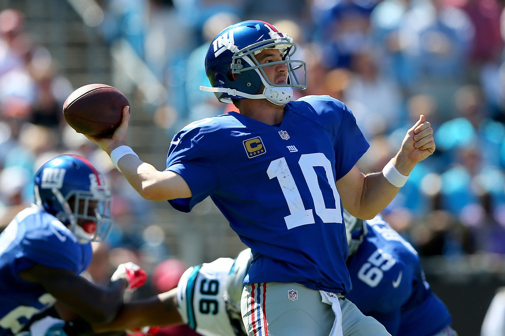 . Eli Manning #10 of the New York Giants drops back to pass against the Carolina Panthers during their game at Bank of America Stadium on September 22, 2013 in Charlotte, North Carolina.  (Photo by Streeter Lecka/Getty Images)