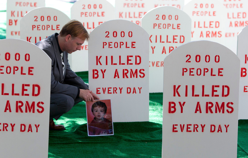 . Control Arms campaigner David Grimason lays a photo of his son Alistair, who was killed by stray bullets in a gun fight, at the base of a mock tombstone which Control Arms coalition set up next to the United Nations building in New York, July 25, 2012. REUTERS/Andrew Kelly/Control Arms/Handout
