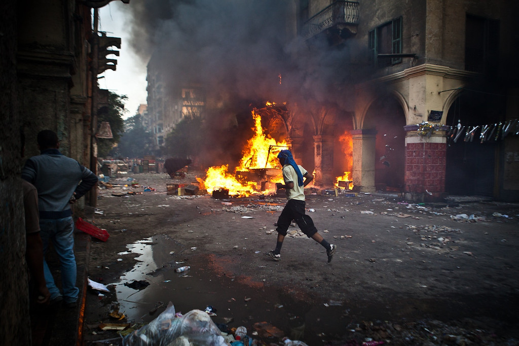 . A supporter of the Muslim Brotherhood and of ousted president Mohamed Morsi runs past a burning vehicle during clashes with security officers close to Cairo\'s Ramses Square, on August 16, 2013. Backers of Egypt\'s ousted president pledged to stage daily demonstrations as they ended a day of angry protests in which at least 75 people were killed during the day. VIRGINIE NGUYEN HOANG/AFP/Getty Images