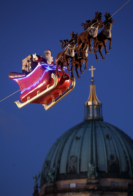 . An actor dressed as Santa Claus waves from a suspended sleigh over a Christmas market as the Dom cathedral stands behind on November 25, 0213 in Berlin, Germany.   (Photo by Sean Gallup/Getty Images)