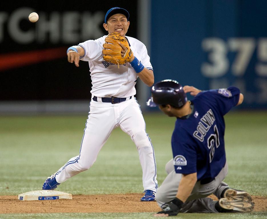 . Toronto Blue Jays Munenori Kawasaki,left, turns a double play on Colorado Rockies Tyler Colvin during a baseball game in Toronto on Monday June 17, 2013.  (AP Photo/The Canadian Press, Frank Gunn)