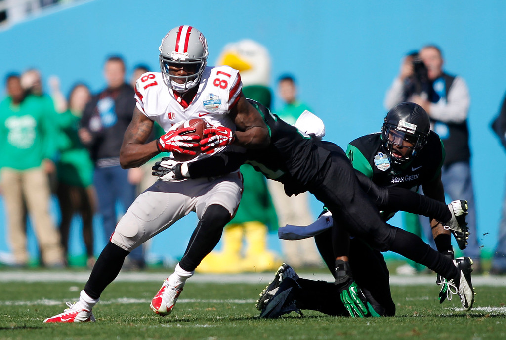 . UNLV wide receiver Devante Davis (81) breaks away from North Texas defensive back Kenny Buyers as linebacker Will Wright, on right, watches during the first half of the Heart of Dallas NCAA college football game, Wednesday, Jan. 1, 2014, in Dallas. (AP Photo/Mike Stone)