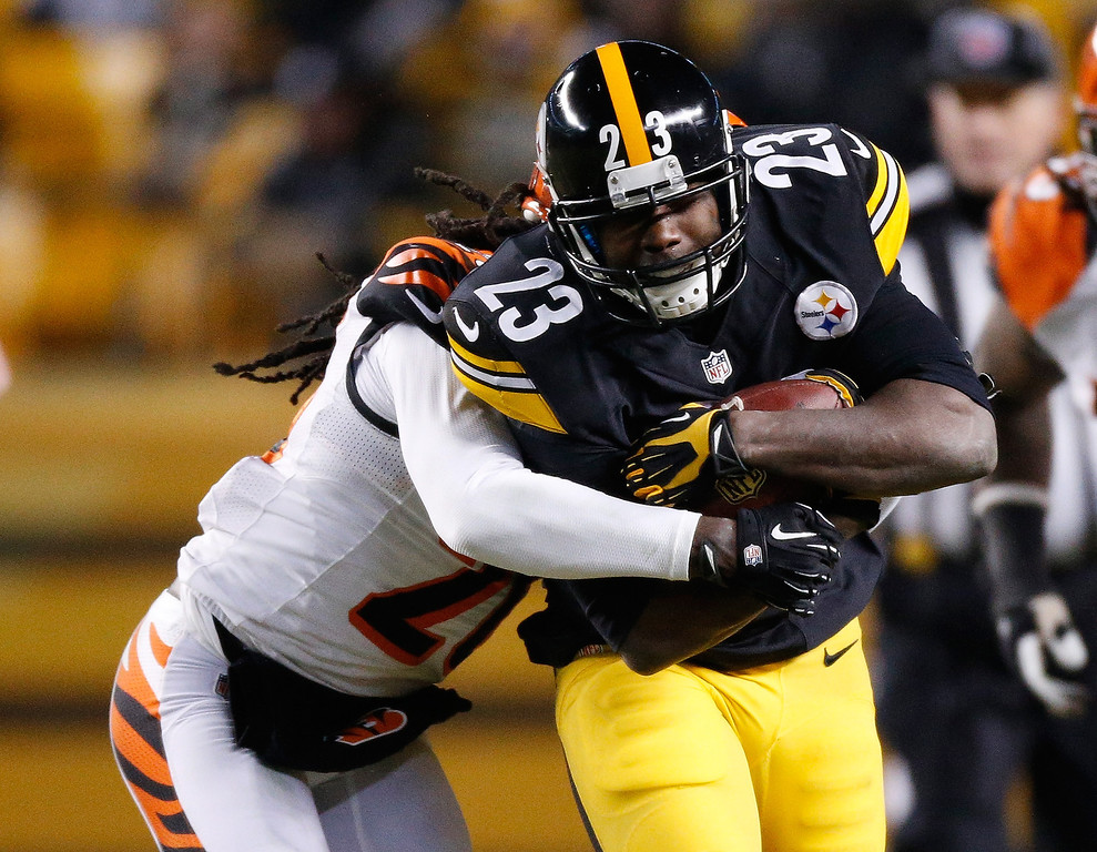 . Felix Jones #23 of the Pittsburgh Steelers tries to get past the tackle of Adam Jones #24 of the Cincinnati Bengals during a second quarter run at Heinz Field on December 15, 2013 in Pittsburgh, Pennsylvania.  (Photo by Gregory Shamus/Getty Images)