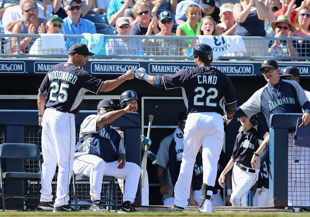 . Robinson Cano #22 of the Seattle Mariners is congratulted by infield coach Chris Woodward #25 after hitting a RBI single against the Colorado Rockies during the fifth inning of the spring training game at Peoria Stadium on March 3, 2014 in Peoria, Arizona.  (Photo by Christian Petersen/Getty Images)