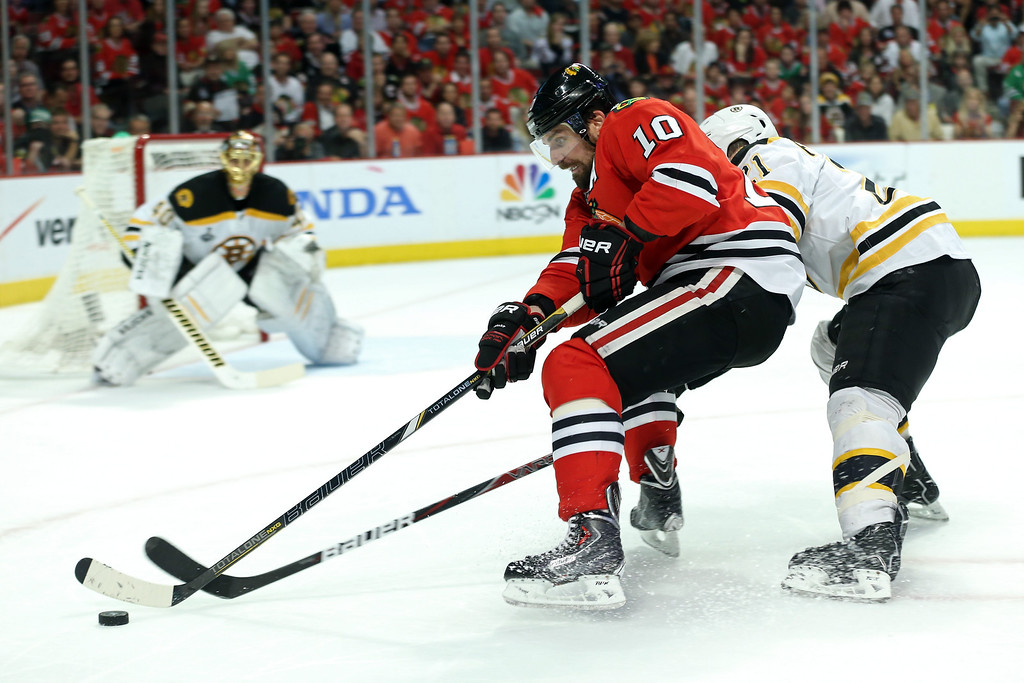 . CHICAGO, IL - JUNE 22:  Patrick Sharp #10 of the Chicago Blackhawks skates for the puck against Andrew Ference #21 of the Boston Bruins in Game Five of the 2013 NHL Stanley Cup Final at United Center on June 22, 2013 in Chicago, Illinois.  (Photo by Bruce Bennett/Getty Images)