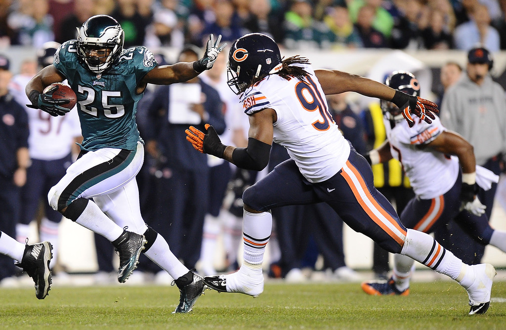 . LeSean McCoy #25 of the Philadelphia Eagles carries the ball with pressure from David Bass #91 of the Chicago Bears during the second quarter at Lincoln Financial Field on December 22, 2013 in Philadelphia, Pennsylvania.  (Photo by Maddie Meyer/Getty Images)