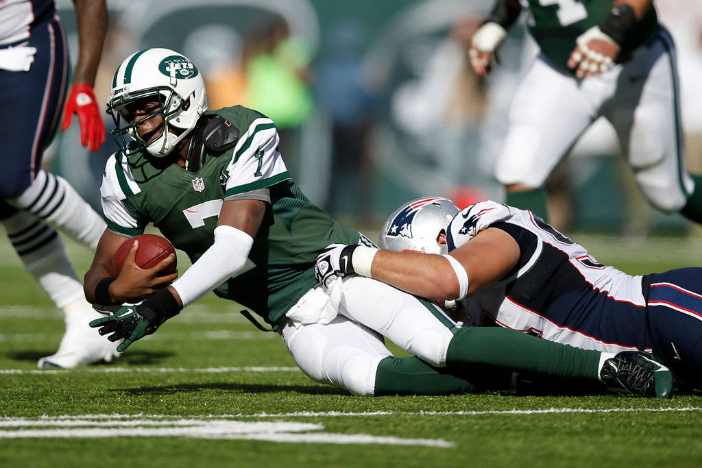 . New York Jets quarterback Geno Smith (7) is sacked by New England Patriots\' Chris Jones, right, during the first half of an NFL football game Sunday, Oct. 20, 2013, in East Rutherford, N.J.  (AP Photo/Kathy Willens)