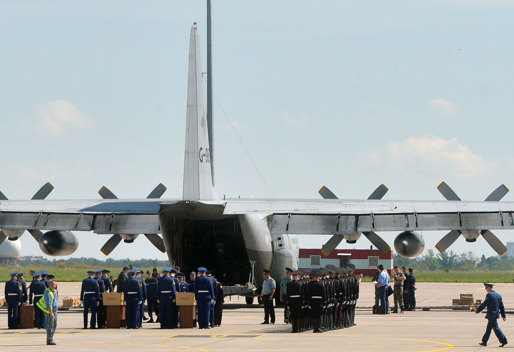 . Ukrainian servicemen carry coffinS that contains the body from downed Malaysia Airlines flight MH17 during a ceremony in Kharkiv on July 23, 2014. The first plane carrying bodies from downed Malaysia Airlines flight MH17 on July 23 left eastern Ukraine for the Netherlands. The Dutch military aircraft took off from the airport in the government-controlled city of Kharkiv bound for Eindhoven after the first group of victims\' remains were loaded onto the plane in wooden coffins. AFP PHOTO/ GENYA  SAVILOV/AFP/Getty Images