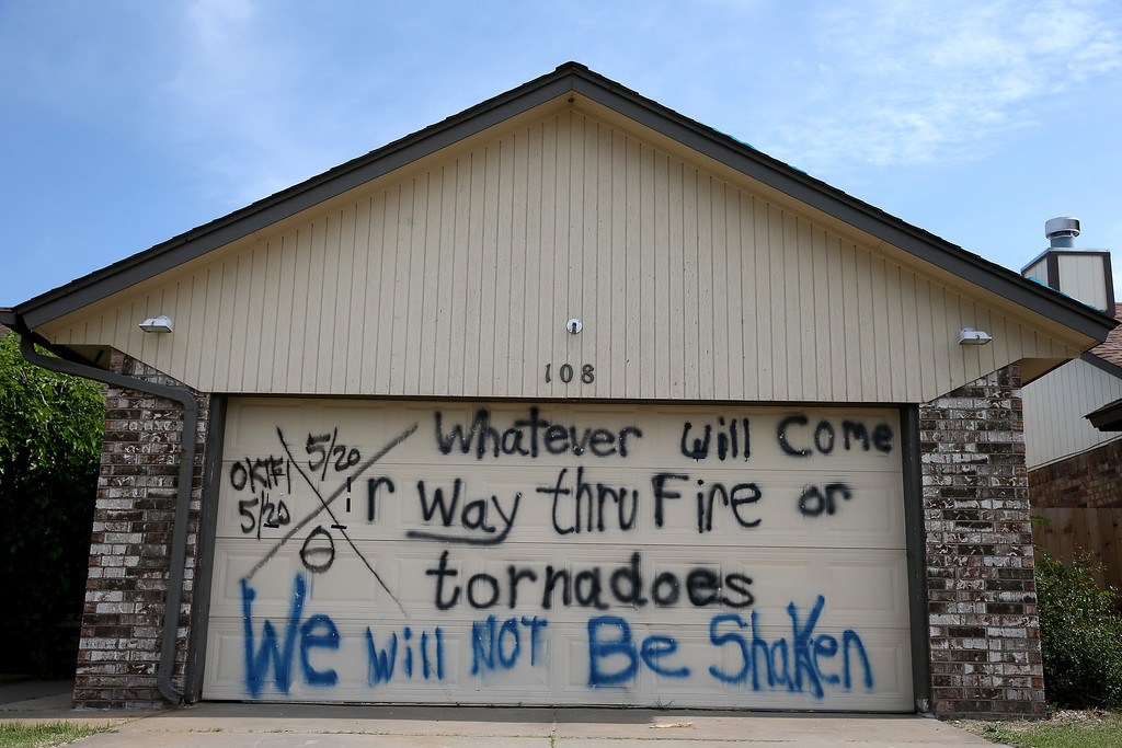 ". A sign reading ""Whatever will come or way thru fire or tornadoes we will not be shaken\"" is seen painted on the garage door of a home as the town prepares for Tuesday\'s one year anniversary of the town being devastated by a tornado on May 18, 2014 in Moore, Oklahoma.  On May 20, 2013, a two-mile wide EF5 tornado touched down in the town, killing 24 people and leaving behind extensive damage to homes and businesses.  (Photo by Joe Raedle/Getty Images)"