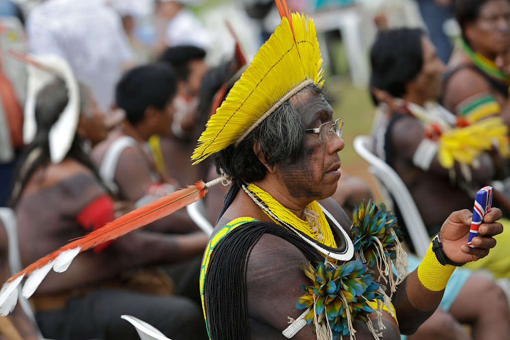 . An Indian from the Kayapo tribe uses his cell phone as he attends the first day of the National Indigenous Mobilization in Brasilia, Brazil, Tuesday, Oct. 1, 2013.  (AP Photo/Eraldo Peres)
